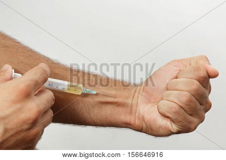 Muscular man injecting steroids on light background, closeup