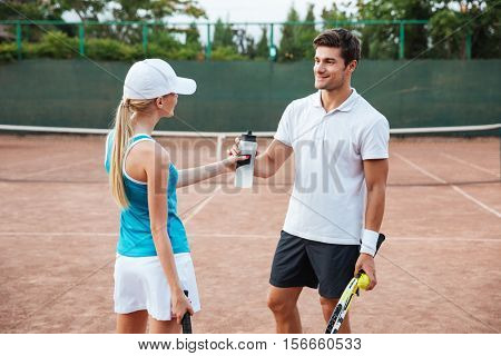Pretty tennis couple on court. drinking water