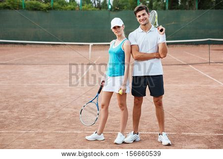 Full length tennis couple on court. looking at camera