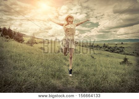 Happiness Female in hat on the green meadow at sunny day in summertime.