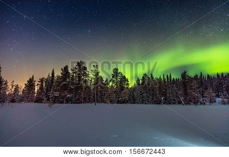Real Northern lights or Aurora borealis above the snow covered forest, winter night landscape, stars sky and beautiful polar lights