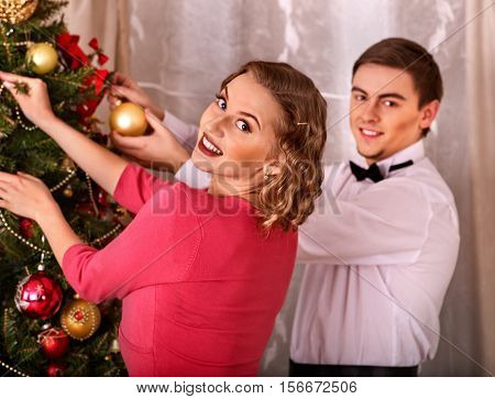 Couple on party near Christmas tree. Black and white retro. Young people decoration Christmas tree.