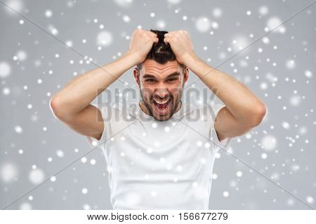 emotions, stress, winter, christmas and people concept - crazy shouting man rending ones hair in t-shirt over snow on gray background