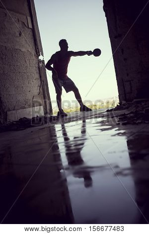 Muscular athletic built young athlete working out with a kettlebell in a ruin building next to a puddle of water