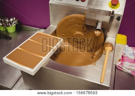 Mould filled with melted chocolate on blending machine in factory