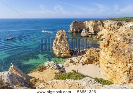 Boats with tourists visiting the caves near the beach of Marinha in Lagoa, Algarve Portugal