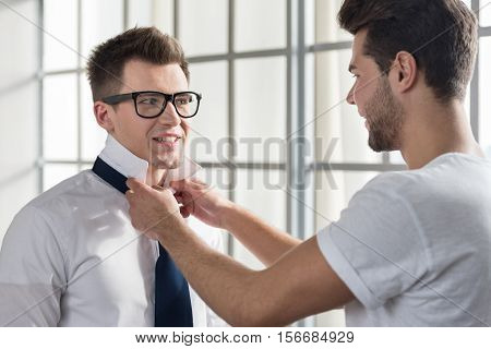 Let me show you. Delighted young man helping his lovely boyfriend and tying a necktie while spending morning together.