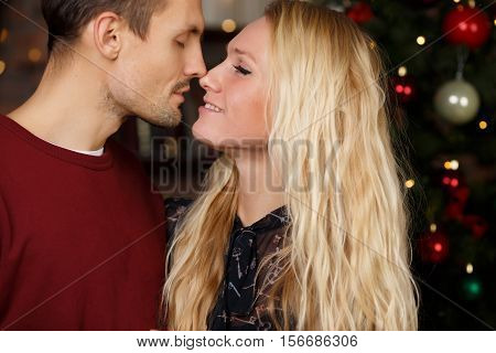 Loving spouses near decorated New Year tree