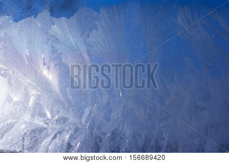 Blue Frost Background, Beautiful Closeup Winter Window Pane Coated Shiny Icy Frost Patterns, Low Temperature, Natural Blue Ice on a Frosty Winter Day