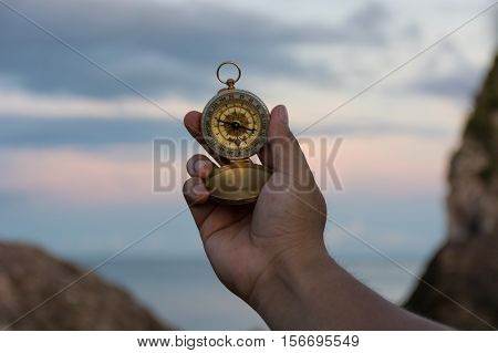 Compass in the hand on the nature background