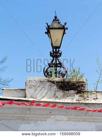Old rusty lantern on the dilapidated white brick wall with trees