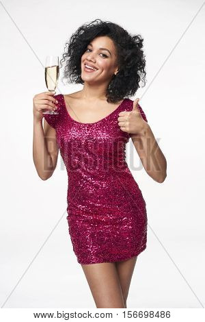 Party, drinks, holidays and celebration concept. Happy mixed race woman in sequined dress with glass of champagne gesturing thumb up hand sign