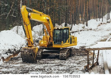 heavy yellow excavator with shovel standing among snowy forest