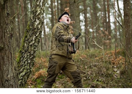 a military man in the woods with a Kalashnikov assault rifle autumn forest with no leaves green form