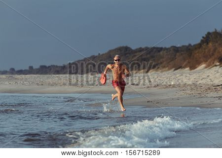 lifeguard on the beach with glasses with a life buoy wet sand and sea at sunset