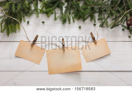 Merry christmas and happy new year decoration, garland frame concept background, top view with copy space on paper sheets at white wood. Winter holidays border from fir tree branches and pine cones
