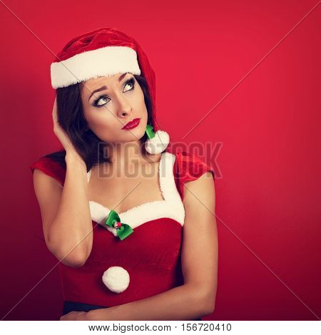 Tired Unhappy Woman In Trouble Looking Up On Empty Copy Space In Christmas Costume On Red Background