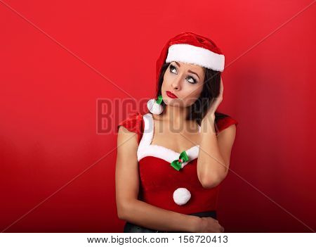 Confused Unhappy Woman In Trouble Looking Uo On Empty Copy Space In Christmas Costume On Red Backgro