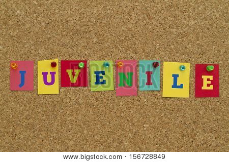 Juvenile word written on colorful sticky notes pinned on cork board.