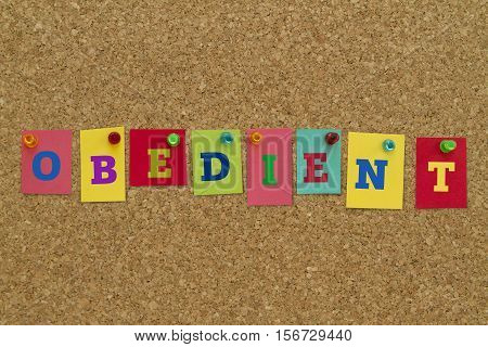 Obedient word written on colorful sticky notes pinned on cork board.