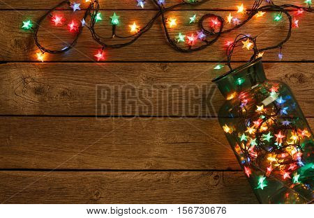 Christmas lights background. Holiday shiny garland border spread from glass jar, top view on brown wooden planks surface. Xmas tree decorations, winter holidays illumination