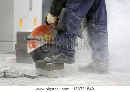 Worker Cutting The Brick Pavers
