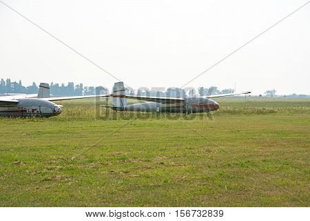 Old gliders parked on the airfield. Picture taken after the rain. Overcast sky covered.