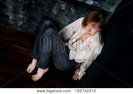 Scared or alarming woman in casual sitting in the corner. Dark toned image top view