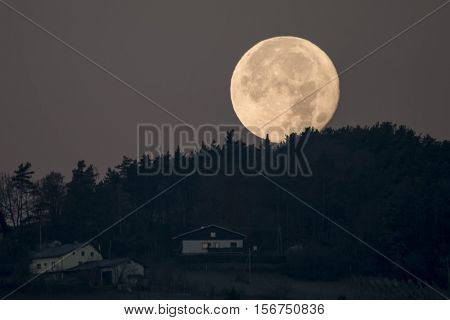 Slovenska Bistrica, Slovenia - November 15 2016: Setting full moon behind hill forest and houses seen on hill. The November supermoon is biggest since 1948 and next is expected in 2034.