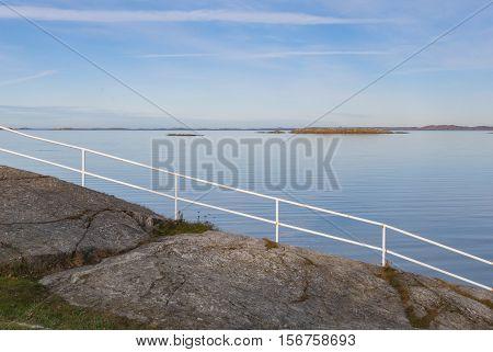 White railing in front of calm sea