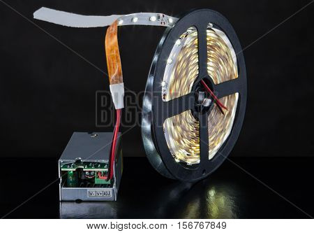 Close-up of luminous LED Light strip wound around a bobbin and a voltage converter on a black background.