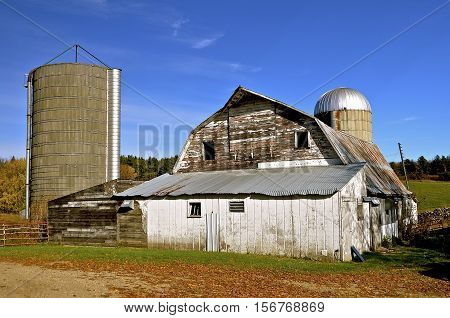 A deserted dairy operation with cement silos, barn, and milking parlor