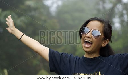 Happy laughing asian teen girl outdoors