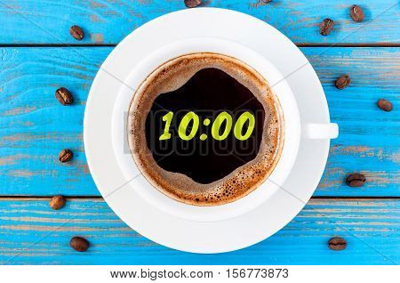 Figures 10 o'clock on morning coffee cup. Start of good day background. Top view, blue wooden surface.
