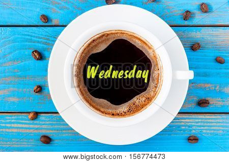 Wednesday - inscription on coffee surface with cup of morning drink. Good day start concept. Top view, blue wooden surface.