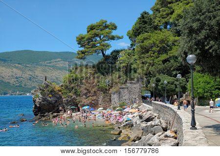 HERCEG NOVI, MONTENEGRO - JULY 18, 2016: small beach crowded of sunbathers along Herceg Novi promenade