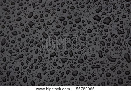 Water drops background with reflected light on the roof of a dark car