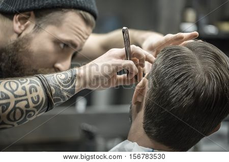 Tattooed bearded barber in a black cap is trimming a clients beard with a straight razor in the barbershop. Closeup. Horizontal.