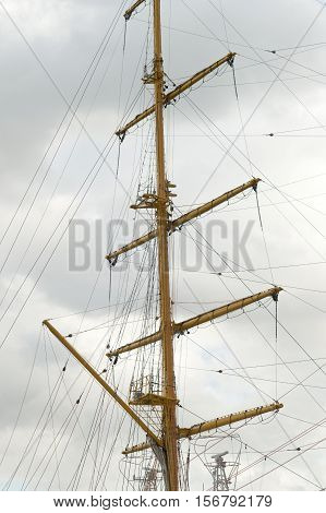 Masts and rigging of a sailing ship against sky and clouds