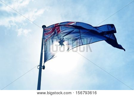 Australian flag blows in the wind against blue sky background