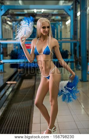 Image of pretty young blonde waving pom-poms at car wash