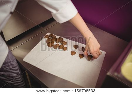 Worker arranging heart shaped chocolates on wax paper in kitchen