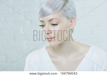 Closeup portrait of daydreaming young woman with short hair.