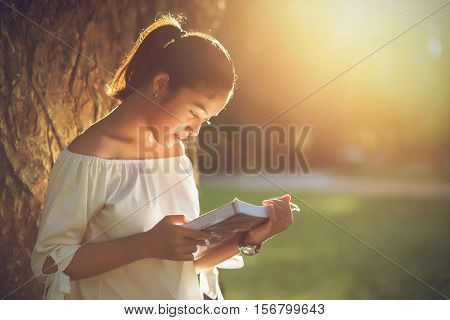 Asian girl reading book at park in summer sunset light. asian woman reading book in Thailand. asian Beautiful woman reading a book at big tree.