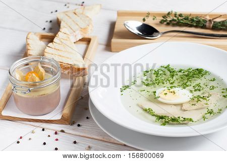 Broth with egg and foie gras on table. Served chicken bouillon with toasts and pate. French cuisine, restaurant menu, luxury food concept