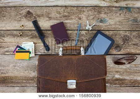 Men accessories: cufflinks, dollars, pen, key, credit card, comb, sunglasses, tablet on wooden background. Top view.