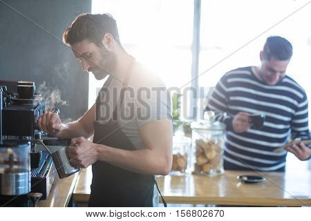 Smiling waiter making cup of coffee in cafe