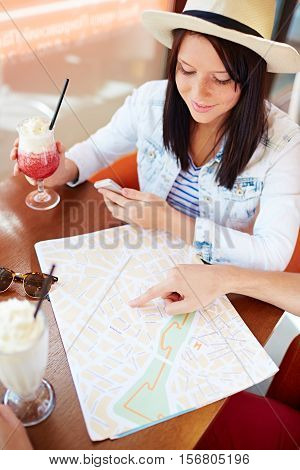 Girl planning travel route with her boyfriend in cafe