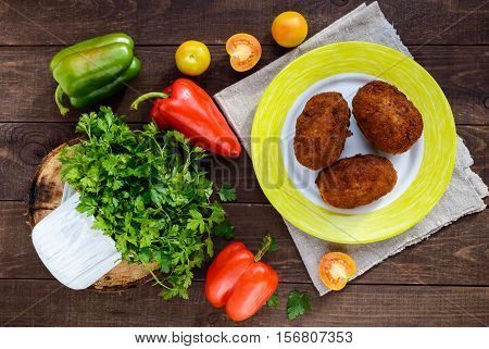 Meat mini-rolls (cutlet) with boiled egg on dark wooden background. The top view.