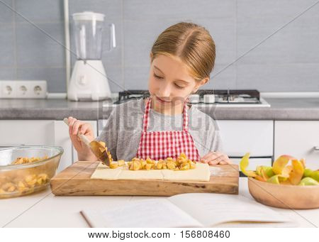 cute little girl putting apple filling with spatula on dough for strudel